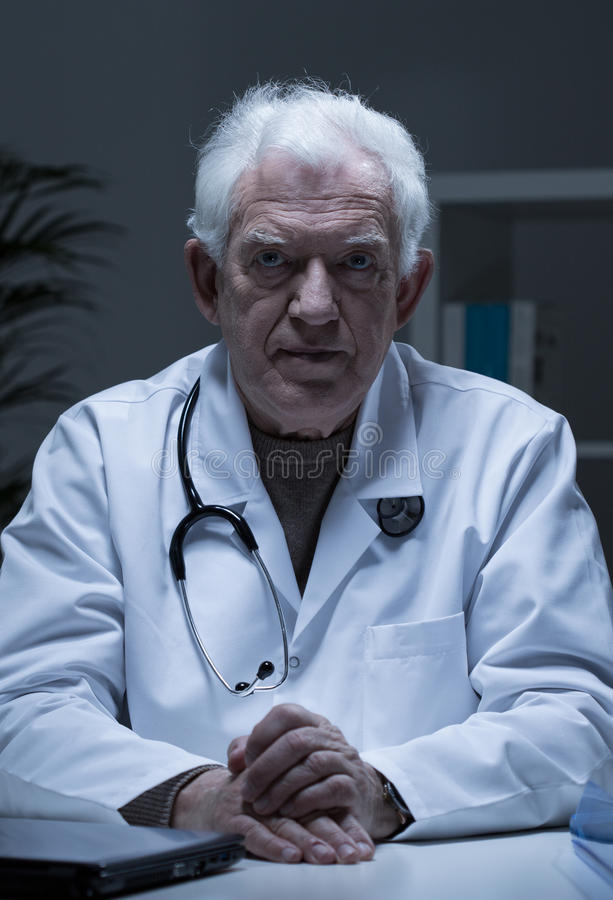Older serious doctor. Portrait of older serious sad doctor in his office royalty free stock photo