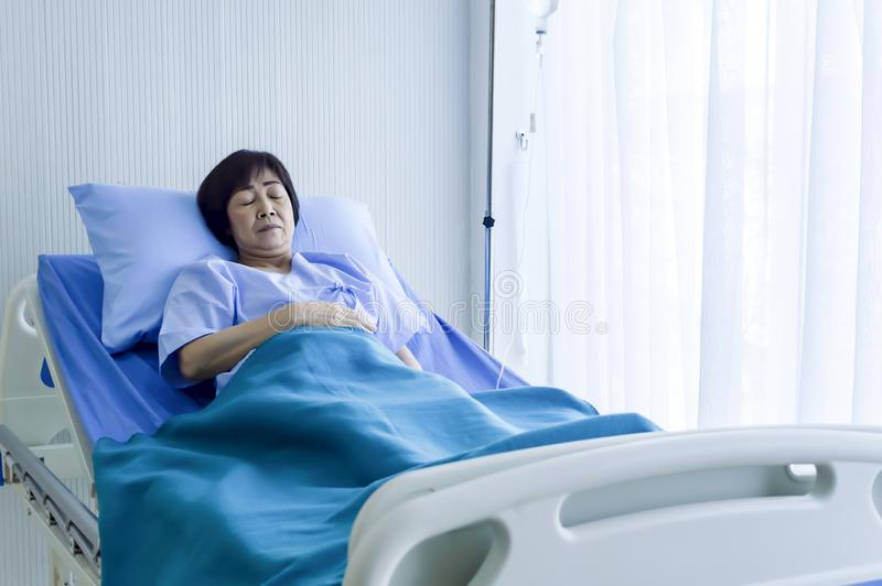 Older sick woman patient lay on bed in hospital with intravenous stock photography