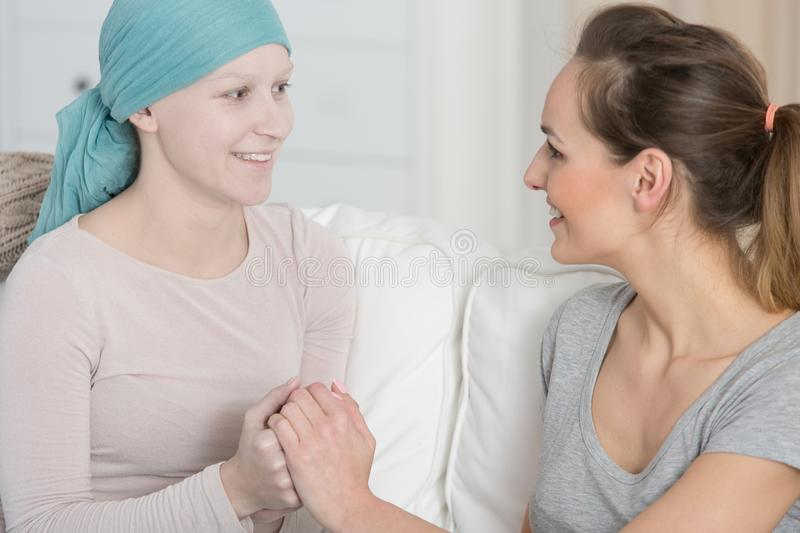 Older sister with family member. Older sister taking on caregiver role at time of diagnosis while sitting with sick family member stock photography