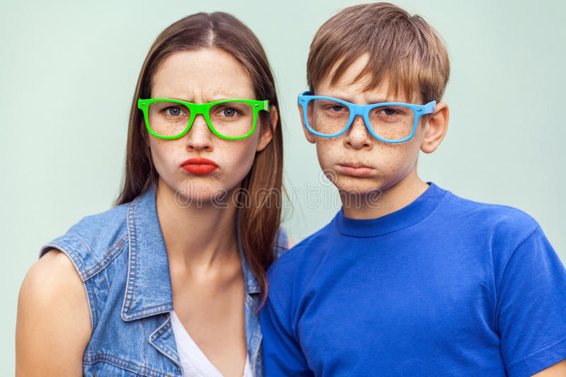 Older sister and her brother with freckles, posing over light blue background together, looking at camera with unhappy faces. royalty free stock photo