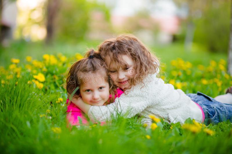 Older sister hug the younger lying in dandelions. Sibling on walk. Girls on glade in spring. royalty free stock image