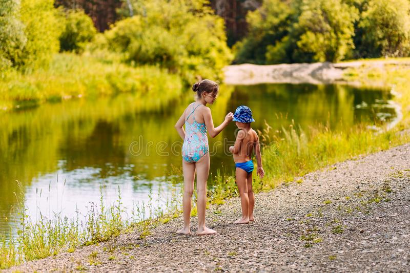 Older sister take care of younger brother. Girl and boy standing on the river. In the summer royalty free stock image