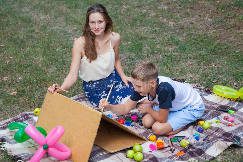 Older sister trying to teach her brother to paint in the park. Older sister trying to teach her brother to paint and posing in the park on summer time, looking royalty free stock photos