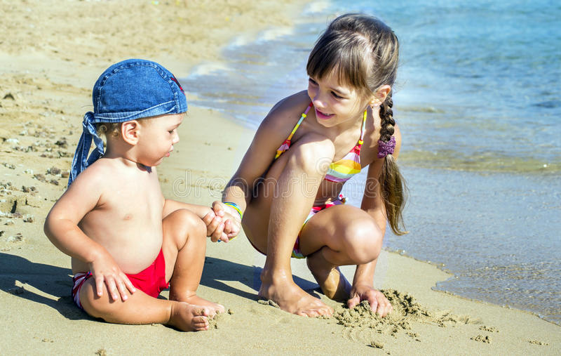 The older sister and younger brother on the seashore look at each other, royalty free stock photo