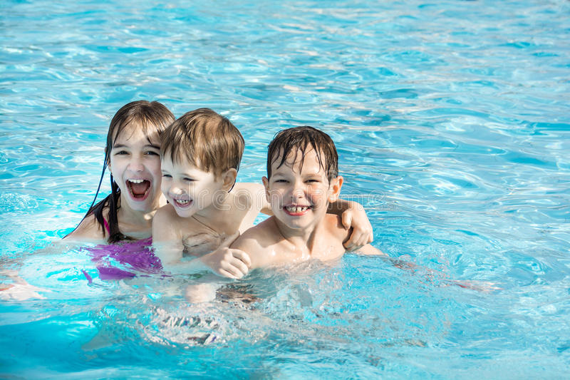 The older sister and younger brothers three are swimming and having fun in the pool with blue water. royalty free stock image