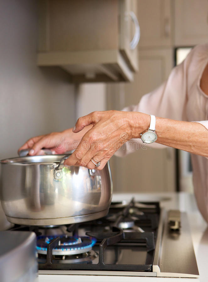Older woman boiling water in pot on stove top royalty free stock photos