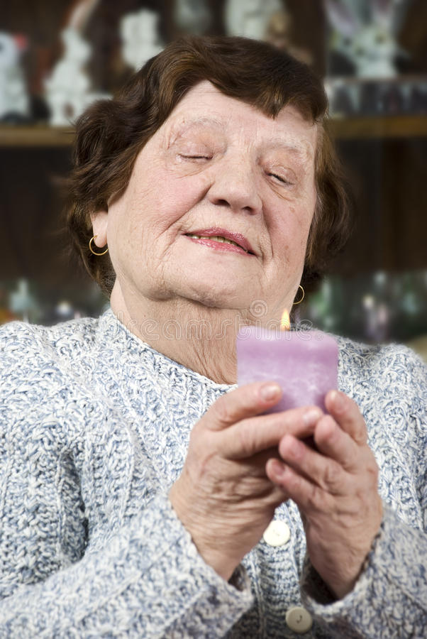 Older woman with candle light. Older woman holding a big candle light and looking down while praying on her home,check also stock image