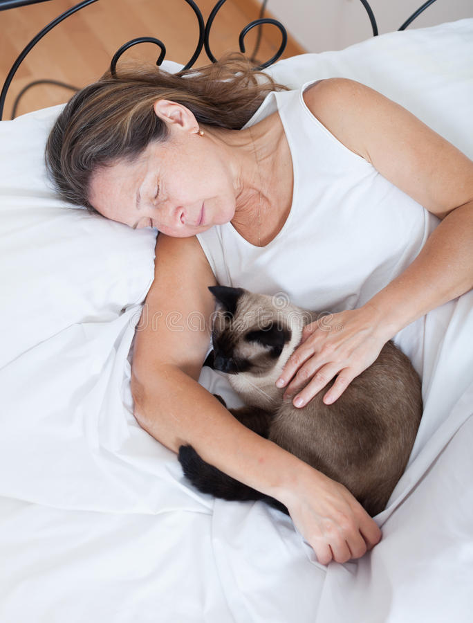 Older woman with cat sleeping royalty free stock photo