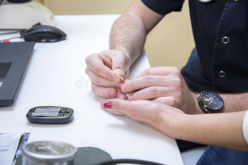 Older woman checking her blood in the clinic stock photos