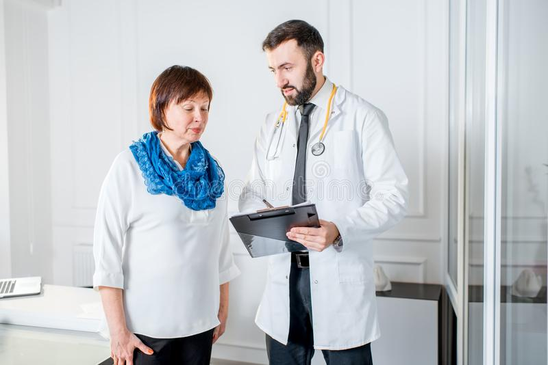 Older woman with doctor in the office. Older women talking with doctor in the office royalty free stock image