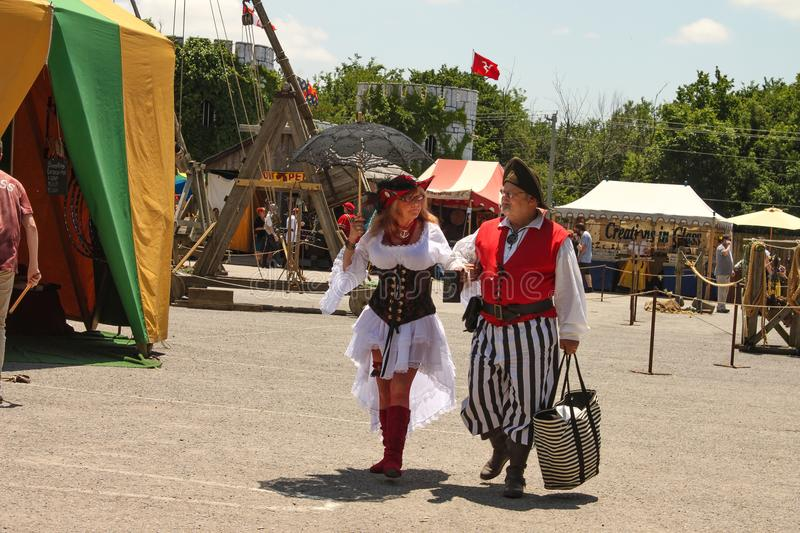 Older woman dressed in very costume and older man dressed as a pirate look at each other fondly as they walk through Renassia stock photography