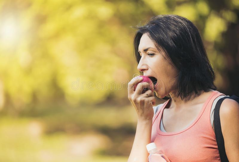 Older woman is eating apple after exercising to take care of the. Ir health.Eat healthy eating concept stock photo