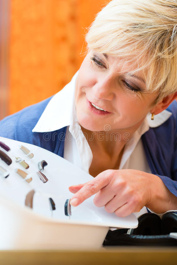 Deaf woman with hearing aid. Older woman or female pensioner with a hearing problem make a hearing test and may need a hearing aid, she looking on a selection of stock images