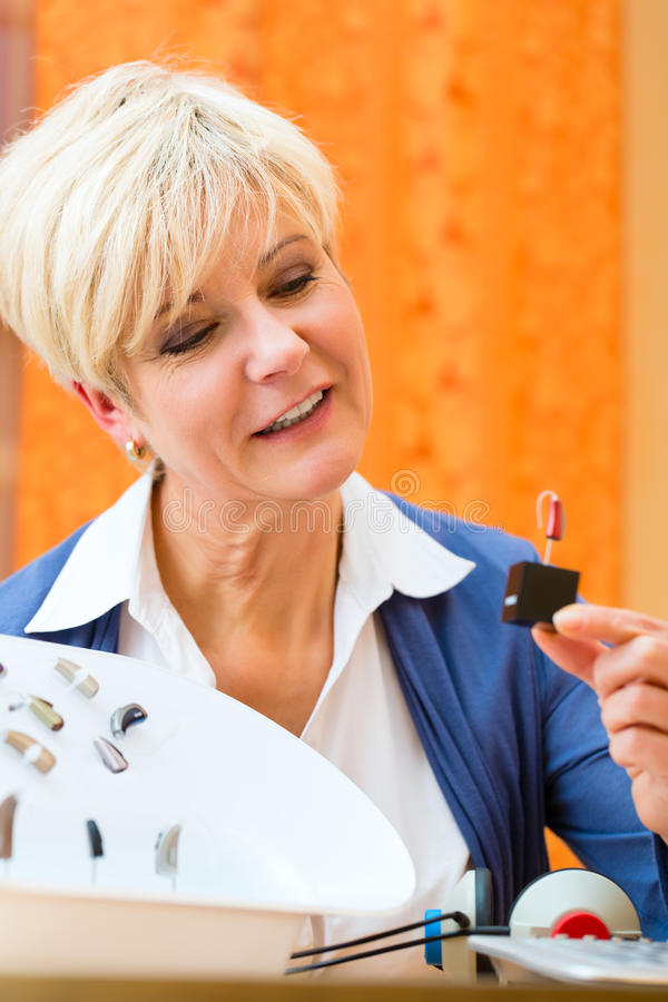 Deaf woman with hearing aid. Older woman or female pensioner with a hearing problem make a hearing test and may need a hearing aid, she looking on a selection of stock image