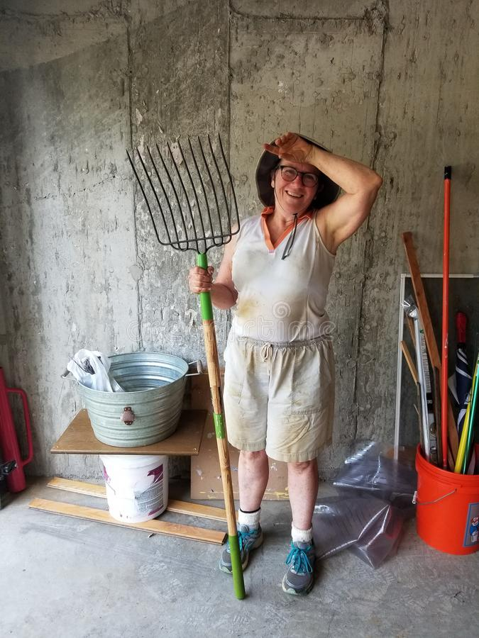 Older woman gardener smiling and holding a pitchfork stock image