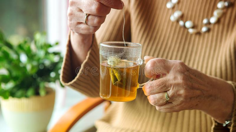 Older woman hand holding a glass of tea royalty free stock photos