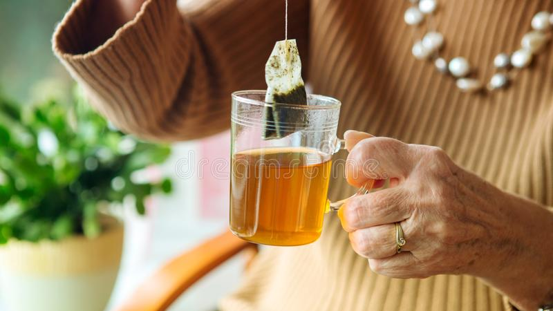 Older woman hand holding a glass of tea royalty free stock image