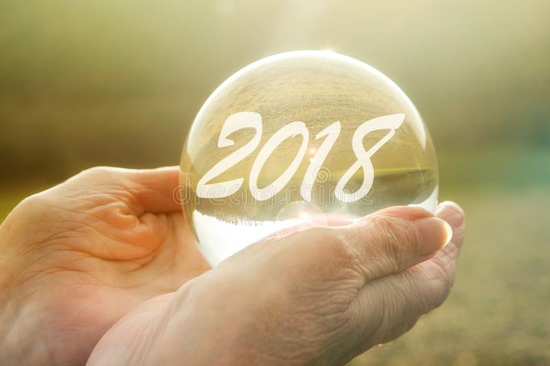 Older woman holding glass sphere with 2018 stock photography