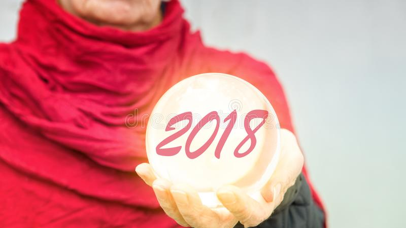 Older woman holding glass sphere with 2018 royalty free stock image