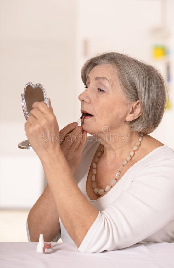 older woman at home looking in the mirror royalty free stock image