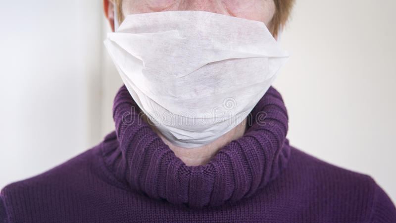 Older woman with a mask protection on against the flu stock image