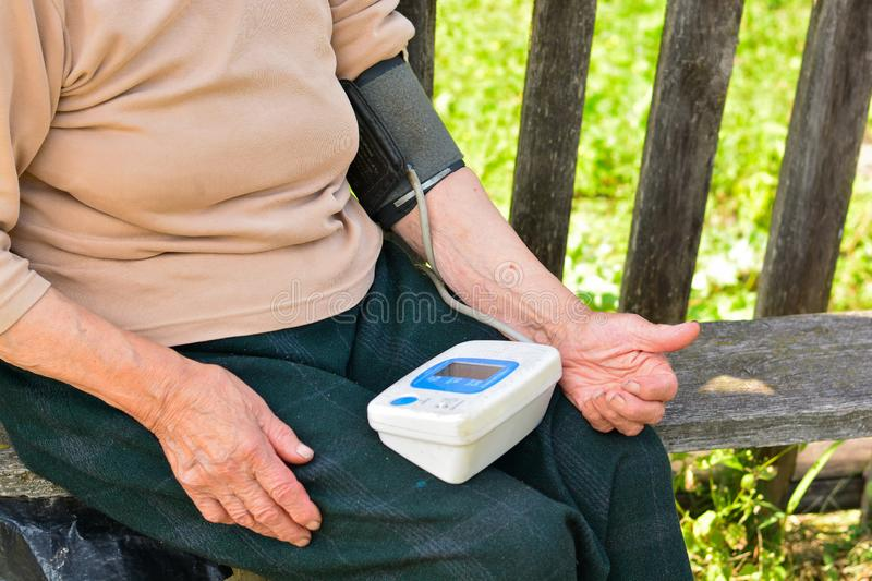 Older woman is measuring blood pressure. Medicine, age, health care and people concept - senior woman with tonometer. Checking blood pressure level stock photos