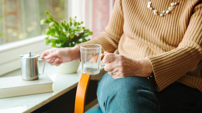 Older woman pouring tea in a glass and sitting by the window stock images
