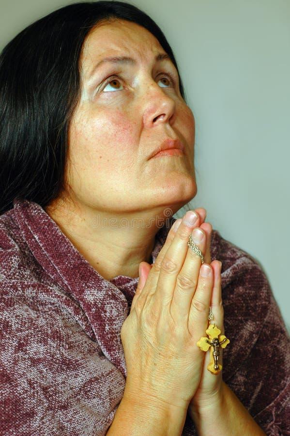 Older woman in prayer royalty free stock image