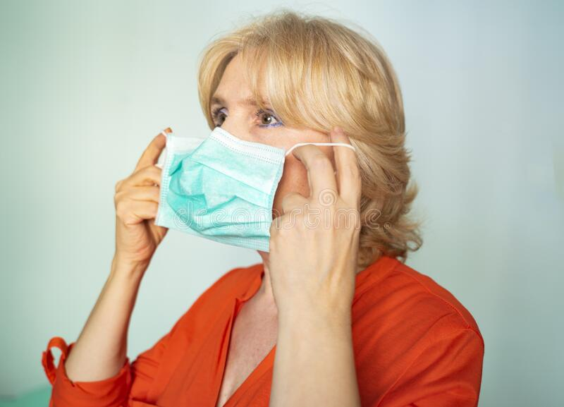 Older woman putting on surgical mask correctly royalty free stock images