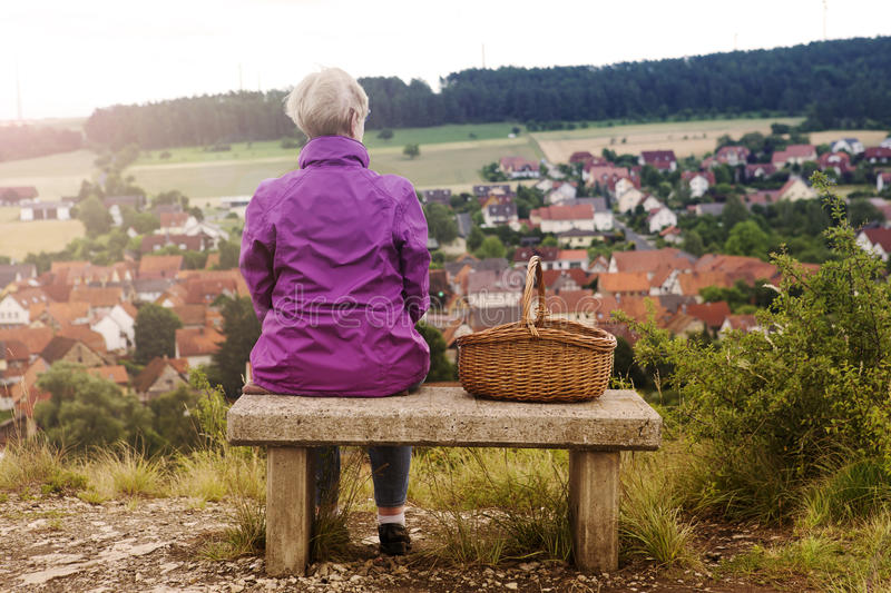 Older woman sitting on bench and looking at small town stock photography