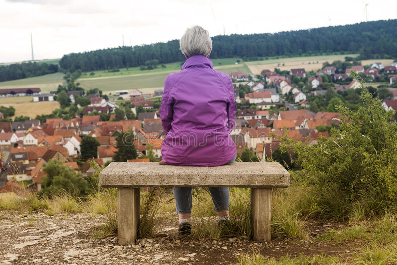 Older woman sitting on bench and looking at town stock photo