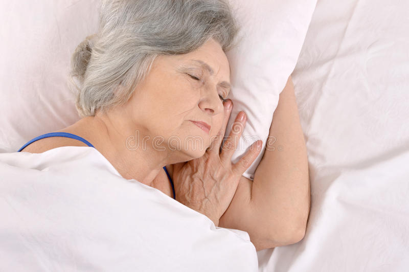 Older woman sleeping in the bedroom. Beautiful older woman sleeping in the bedroom royalty free stock photo