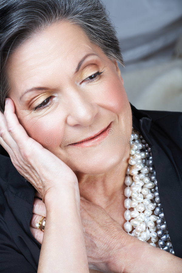 Older woman smiling in 70s. Beautiful smiling older woman with short black and grey hair and pearl necklace in her 70s royalty free stock images