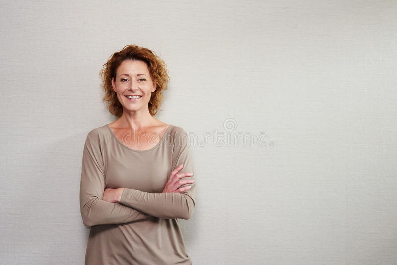Older woman smiling with arms crossed by wall royalty free stock photos