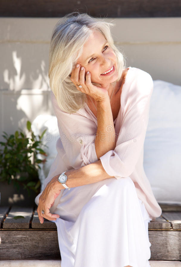 Older woman smiling and sitting on porch outside. Portrait of older woman smiling and sitting on porch outside royalty free stock photo
