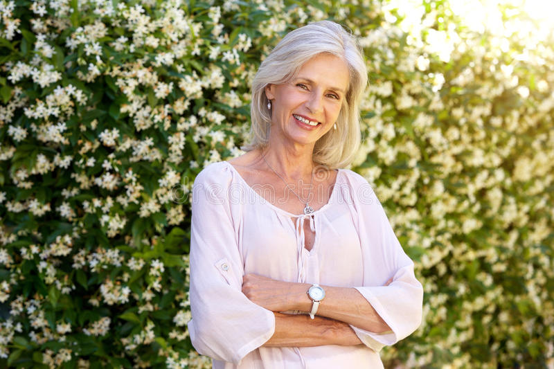 Older woman smiling and standing outside in spring stock image