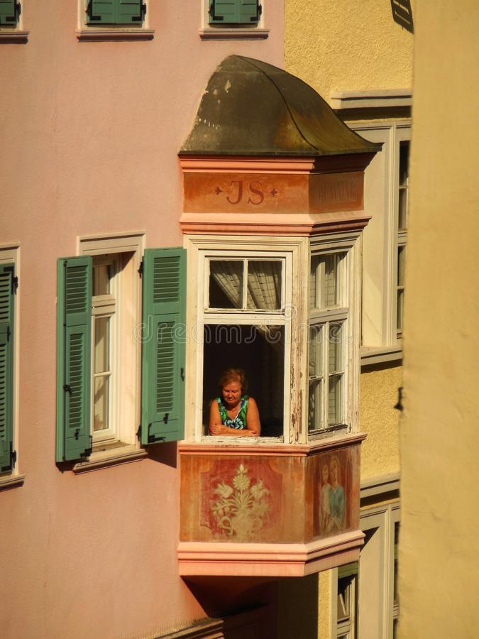Woman in the Window, Bolzano, Italy. An older woman suns herself in the window of an apartment building in the northern Italian city of Bolzano located in the stock images