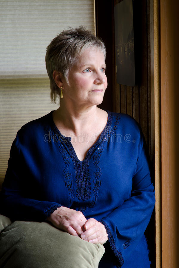 Older woman by window light stock images