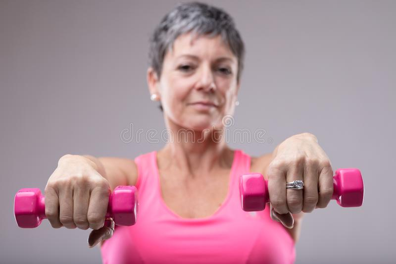 Older woman working out with a pair of dumbbells royalty free stock photography