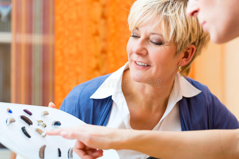 Deaf woman with hearing aid. Older women or female pensioner with a hearing problem make a hearing test and may need a hearing aid, she looking on a selection of stock images