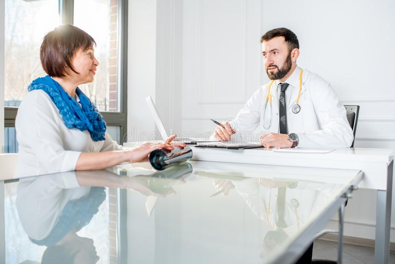 Older woman with doctor at the office. Older women having a medical consultation with male doctor sitting at the white office royalty free stock photo