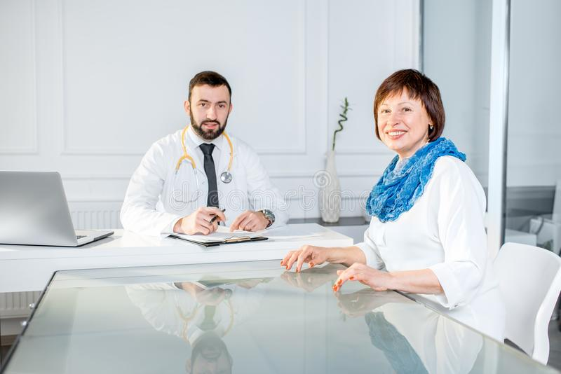 Older woman with doctor at the office. Older women having a medical consultation with male doctor sitting at the white office stock photos