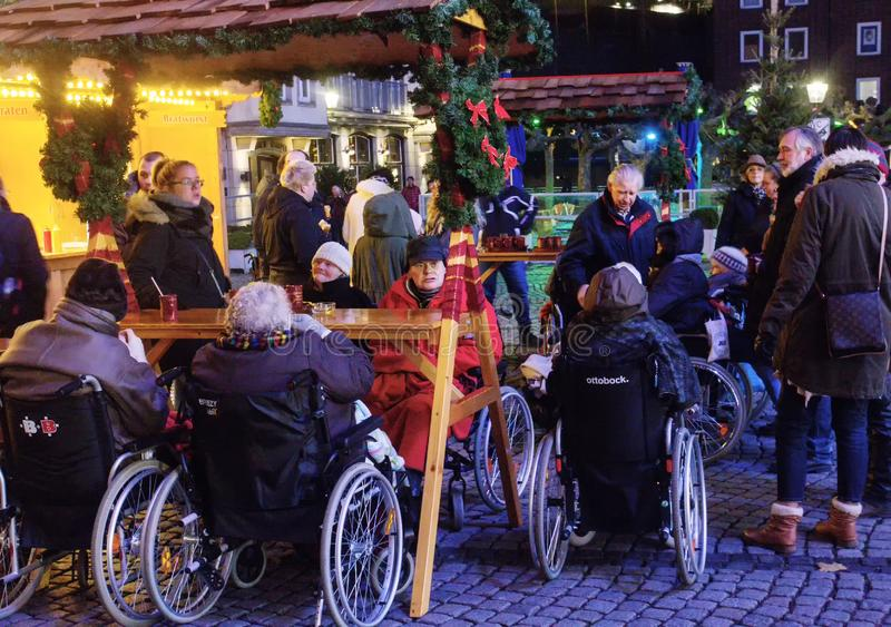 Older women with limited mobility in wheelchairs using muscular arm strength drink mulled wine surrounded by relatives. Christmas stock photo
