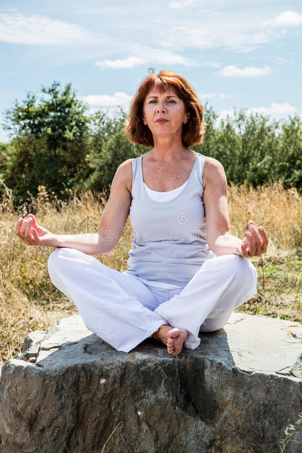 Older yoga woman seeking for spiritual peace. Breathing outside - older yoga woman sitting on a stone exercising,seeking for spiritual peace with tree background royalty free stock images