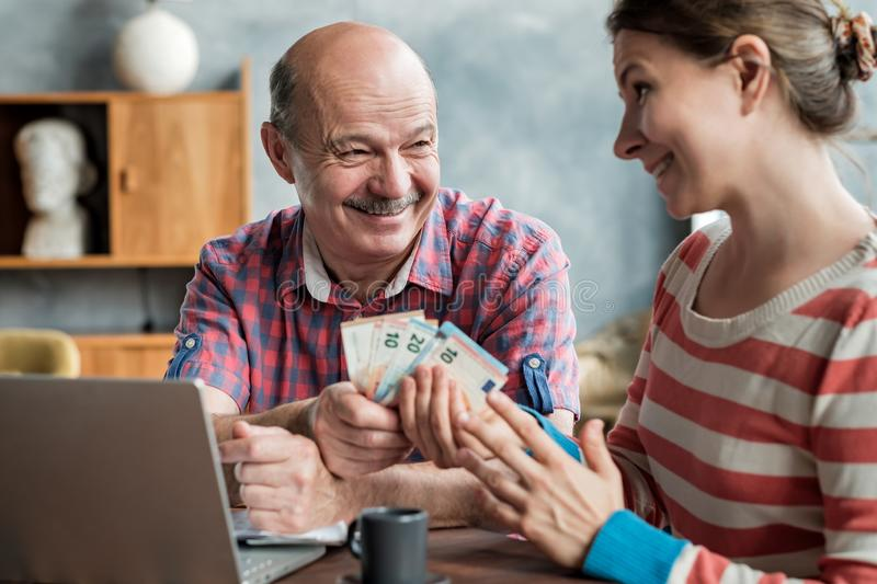 Olderly Spanish man gives his daughter money for a mortgage or student loan. royalty free stock image