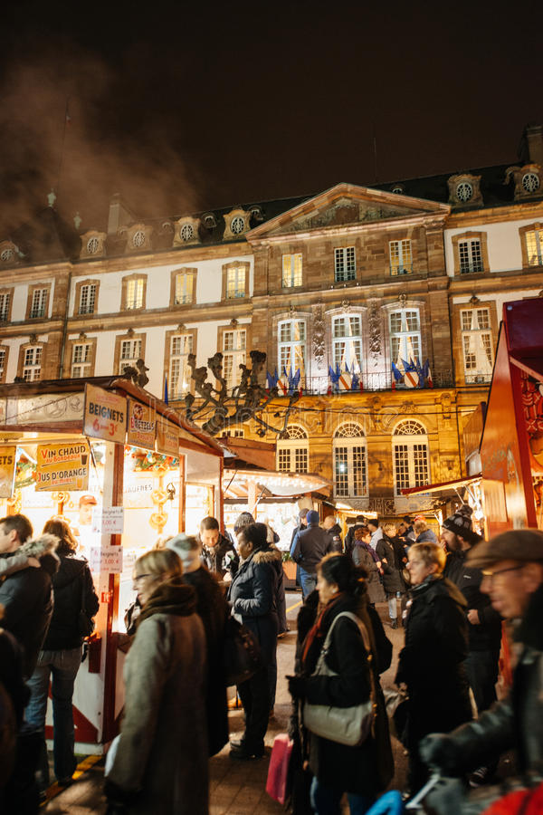 The oldest Christmas Market in Europe - Strasbourg, Alsace, Fran. STRASBOURG, FRANCE - DEC 5, 2014: Strasbourg City Hall seen through Christmas Market visitors royalty free stock photography