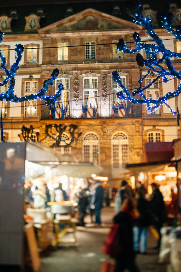 The oldest Christmas Market in Europe - Strasbourg, Alsace, Fran. STRASBOURG, FRANCE - DEC 5, 2014: Strasbourg City Hall seen through Christmas Market visitors royalty free stock photos
