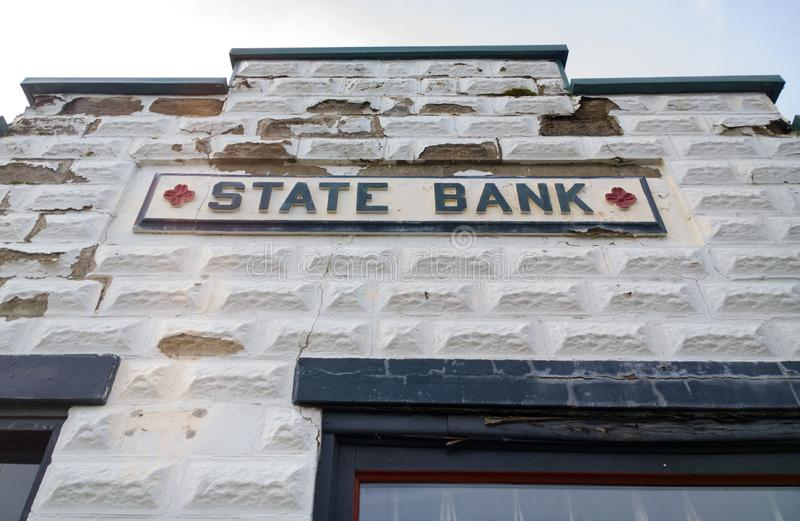 Oldie But Goodie. Original architectural facade, paint cracking and blocks peeling, of an old state bank stock photo