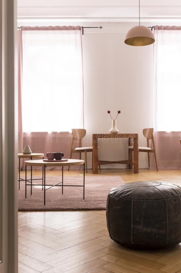 Oldschool leather pouf in stylish living room interior with two coffee table and pastel pink carpet on parquet floor. Oldschool leather pouf in stylish living royalty free stock photography