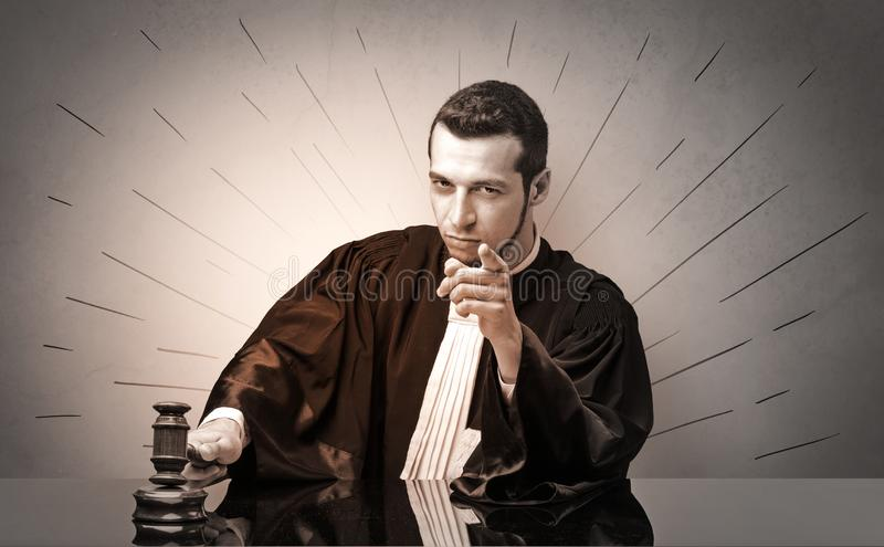 Oldscool young judge in gown deciding. Young dashing judge in black gown making decision stock photo